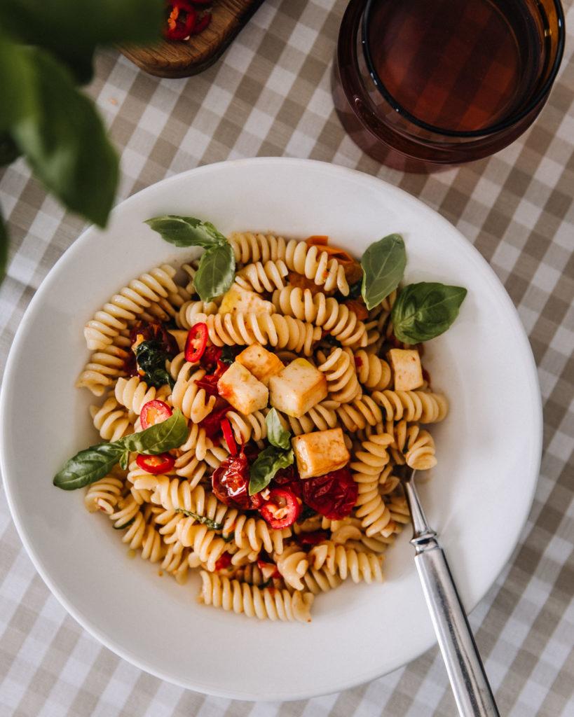 Halloumipasta on valkoisella syvällä lautasella. Kierrepasta, halloumikuutiot, uunissa paahdetut tomaatit ja basilikanlehdet ovat ihana yhdistelmä. Pöytäliina on ruudullinen.