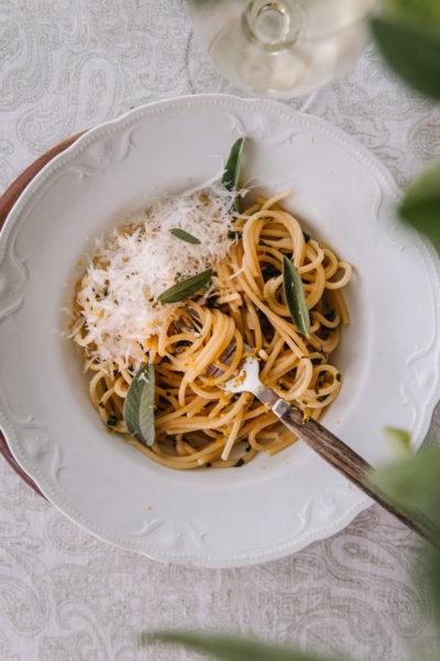 """Salviapasta on valkoisella, syvällä lautasella. Lautasen reunalla on kohokuvioita. Pastan päällä on hieman parmesaania sekä muutama pieni salvian lehti. Kuvan oikeassa reunassa on """"blurrina"""" salvianlehtiä."""