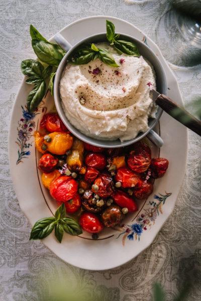 Vaahdotettu feta on pyöreässä pienessä astiassa, joka on soikealla vadilla. Vadilla on lisäksi uunissa paahdettuja kirsikkatomaatteja, kapriksia ja basilikaa.