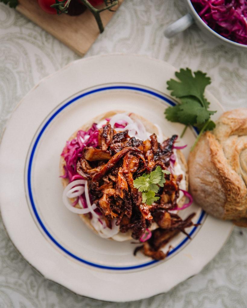 Nyhtösienet on laitettu sämpylän päälle. Sienien lisäksi burgerissa on maustettua punakaalia, majoneesia, ohuita sipulirenkaita sekä korianteria.  Burgeri on vaalealla lautasella, jossa on sininen raita.