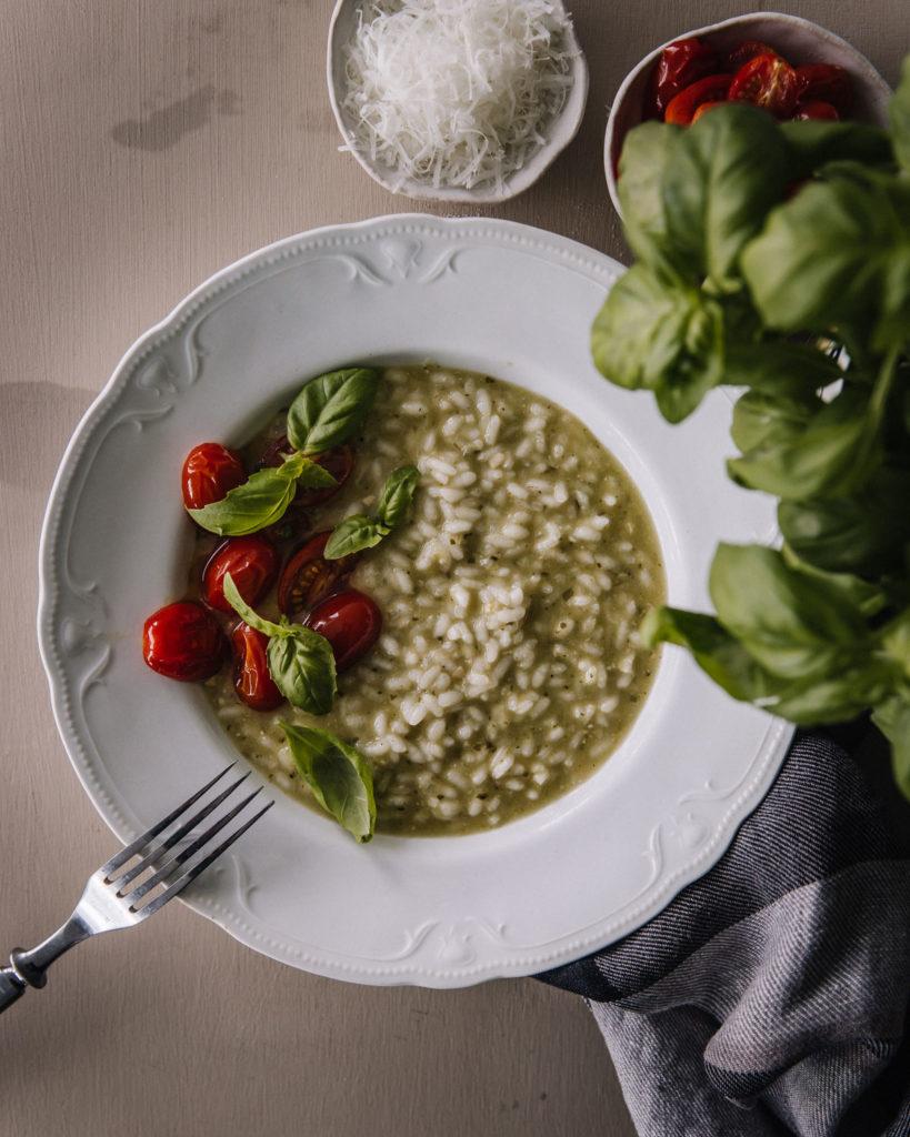 Pestorisotto on valkoisella vanhalla lautasella, jossa on reunalla kohokuvioita. Risoton päällä on paahdettuja kirsikkatomaatin puolikkaita sekä basilikanlehtiä. Kuvan ylälaidassa on pienissä kupeissa pecorino-raastetta ja em. tomaatteja.
