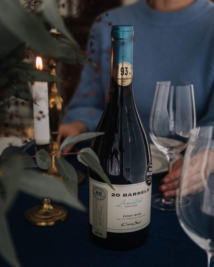 Cono sur 20 Barrels Pinot Noir on chileläinen punaviini. Kuvassa on pullo ja taustalla on nainen, joka pitelee kädessään tyhjää viinilasia (ehkä toivoo siihen täytettä).