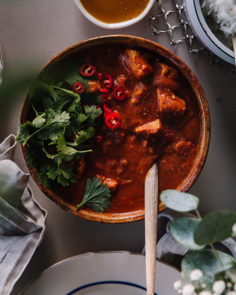 Tofucurry on ruskeassa keraamisessa kulhossa. Tomaattisen kastikkeen päällä on tuoretta chiliä siivuina sekä korianteria. Kattauksessa on myös riisikattilan kulma sekä mangososetta pienessä kipossa.